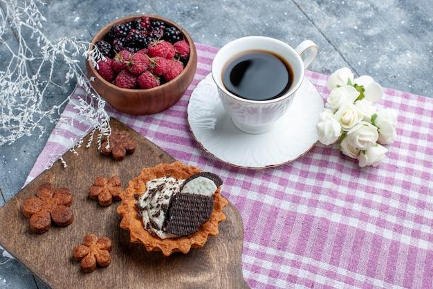 Bovenaanzicht van kom met bessen vers en rijp fruit met koekjes en koffie op licht bureau, bessen fruit vers zacht bos