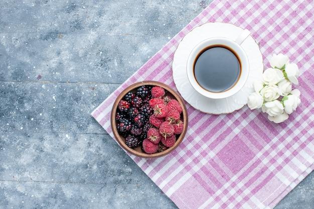 Bovenaanzicht van kom met bessen vers en rijp fruit met koffie op grijs, bessen fruit vers rijp zacht bos