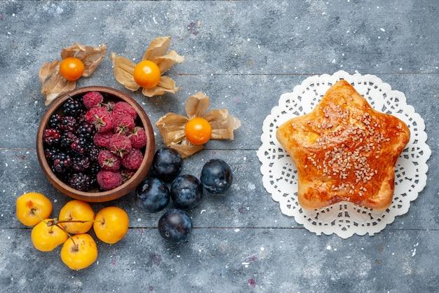 Bovenaanzicht van kom met bessen vers rijp fruit met gebak op grijs, bessen fruit vers zacht bos