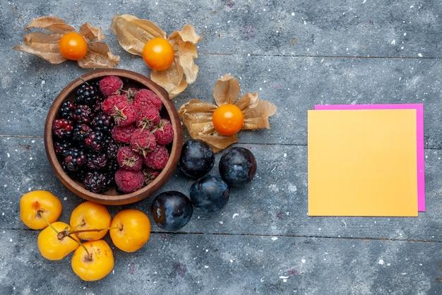 Bovenaanzicht van kom met bessen vers rijp fruit met gele kersen en pruimen op grijs, bessen fruit vers zacht bos