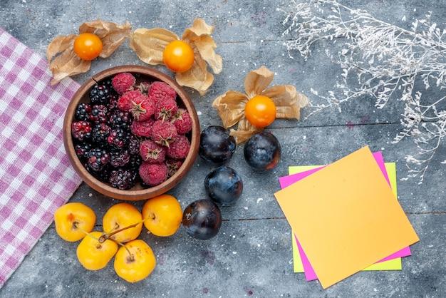 Bovenaanzicht van kom met bessen vers rijp fruit met gele kersen en pruimen op grijs rustiek, bessen vers zacht bos