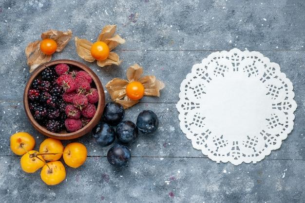 Bovenaanzicht van kom met bessen vers rijp fruit op grijs houten, bessen fruit vers zacht bos
