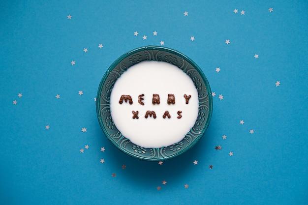 Bovenaanzicht van kom met melk en chocolade alfabet granen. vrolijke xmas tekst.