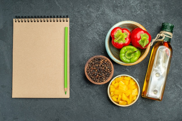 Bovenaanzicht van kom met paprika aan de rechterkant met kruiden- en groenteschalen, oliefles en blocnote aan kant op groene tafel