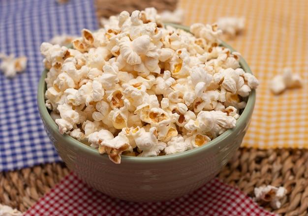 Bovenaanzicht van kom met popcorn over kleurrijke keukendoeken en een strotafel