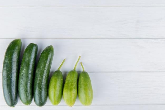 Bovenaanzicht van komkommers aan de linkerkant en hout met kopie ruimte