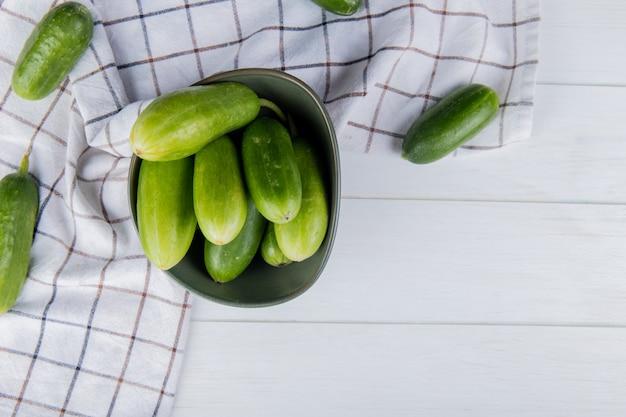 Bovenaanzicht van komkommers in kom met andere op geruite doek en houten oppervlak