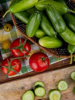 Bovenaanzicht van komkommers in mand met tomaten op doek en komkommer plakjes op hout