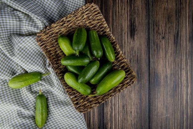Bovenaanzicht van komkommers in mand plaat met andere op doek en hout met kopie ruimte