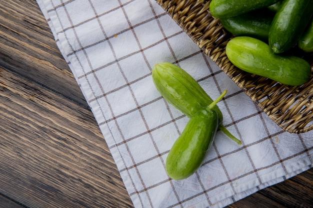 Bovenaanzicht van komkommers in mand plaat met andere op doek en hout