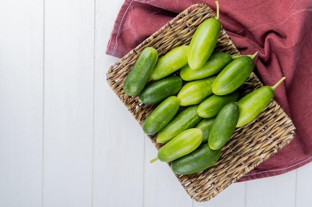 Bovenaanzicht van komkommers in mand plaat op bordo doek aan de rechterkant en hout met kopie ruimte