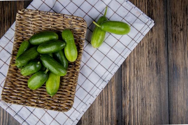 Bovenaanzicht van komkommers in mand plaat op doek en hout