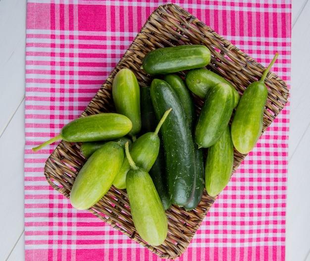 Bovenaanzicht van komkommers in mand plaat op geruite doek en wit