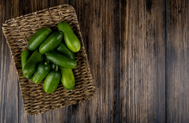 Bovenaanzicht van komkommers in mand plaat op hout met kopie ruimte