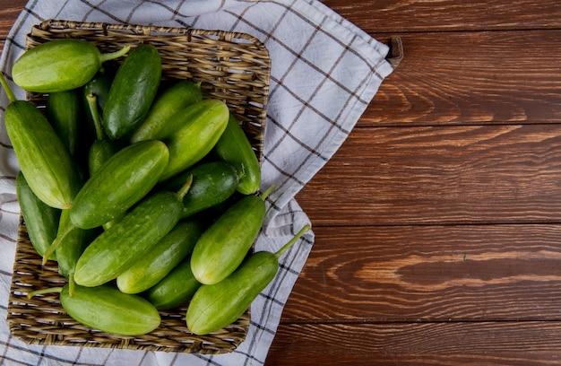 Bovenaanzicht van komkommers in mand plaat op plaid doek en hout met kopie ruimte