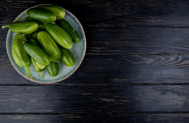 Bovenaanzicht van komkommers in plaat op hout met kopie ruimte