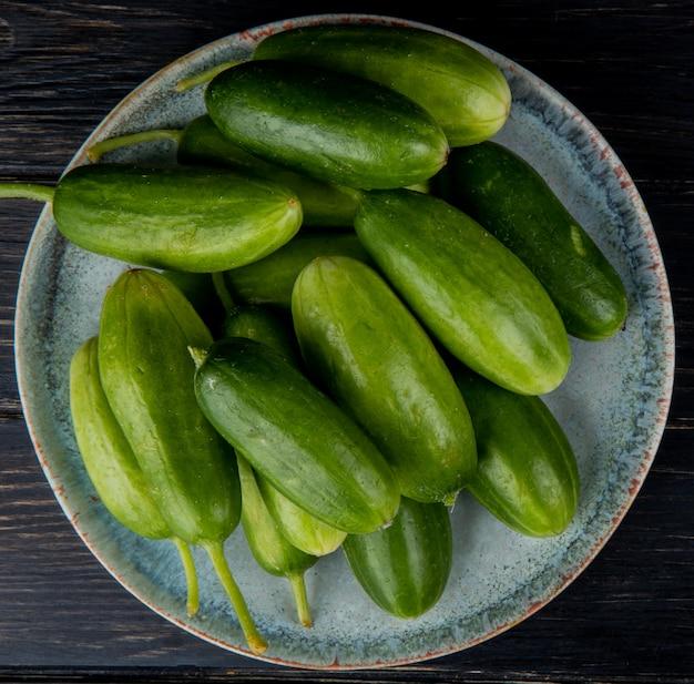 Bovenaanzicht van komkommers in plaat op hout