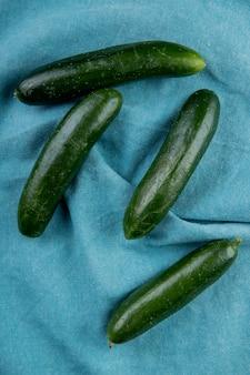 Bovenaanzicht van komkommers op blauw doek
