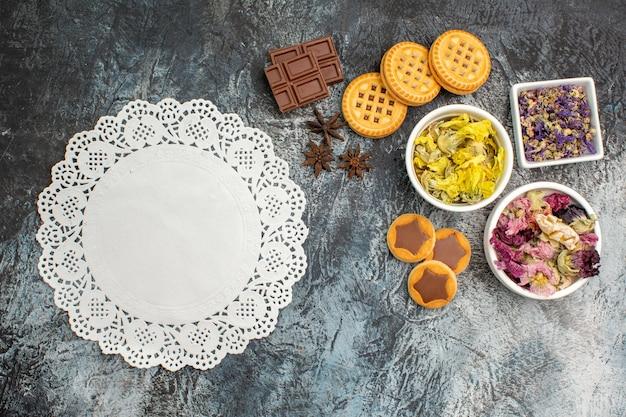 Bovenaanzicht van kommen met droge bloemen met chocolade en koekjes met wit kant op grijze achtergrond