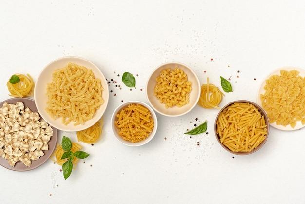 Bovenaanzicht van kommen met verschillende soorten pasta