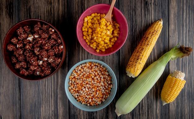 Bovenaanzicht van kommen vol chocolade popcorn met gekookte en gedroogde maïs zaden en likdoorns op hout