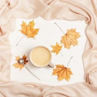 Bovenaanzicht van kopje koffie cappuccino met melkschuim, warme stoffen sjaal en gele herfst seizoen bladeren van esdoorn op witte houten tafel