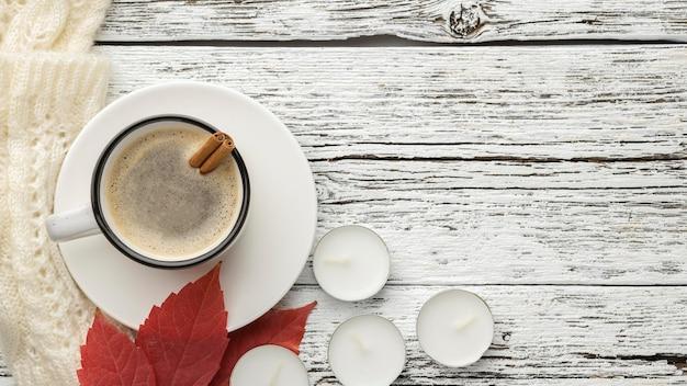 Bovenaanzicht van kopje koffie met blad en kaarsen