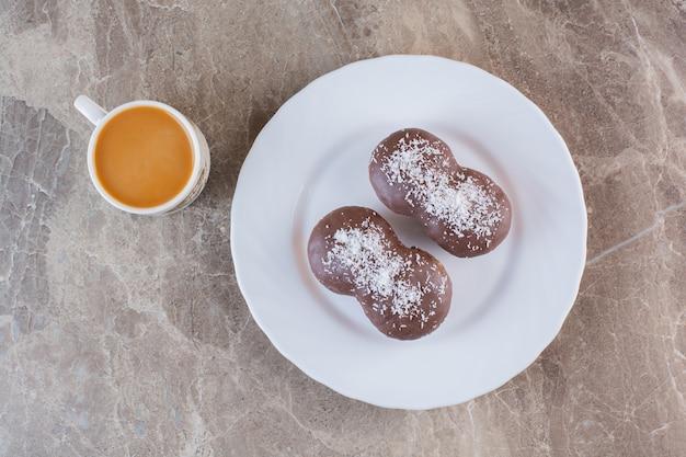 Bovenaanzicht van kopje koffie met chocoladekoekjes op witte plaat.