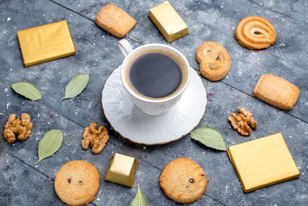 Bovenaanzicht van kopje koffie met koekjes, walnoten op grijs bureau, cookie koekje zoet