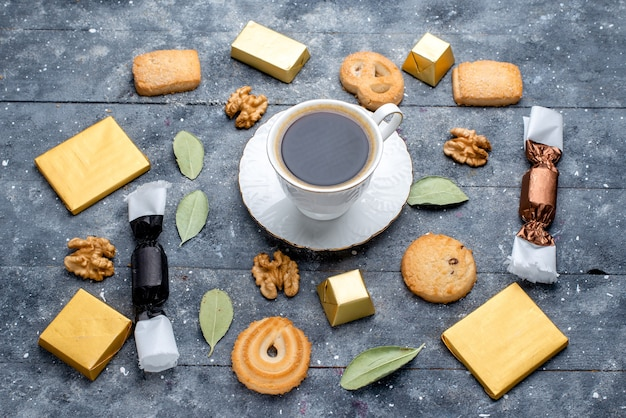 Bovenaanzicht van kopje koffie met koekjes, walnoten op grijs, cookie biscuit zoete bak