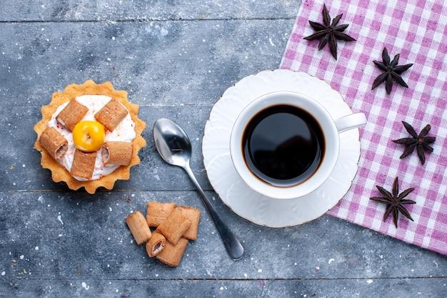 Bovenaanzicht van kopje koffie met kussen gevormde koekjes en romige cake op helder bureau, koffiekoekje biscuit zoet deeg