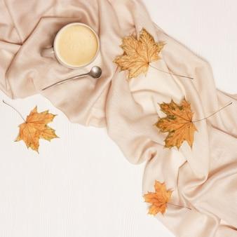 Bovenaanzicht van kopje koffie met melkschuim, warme stoffen sjaal en gele herfst seizoen bladeren van esdoorn