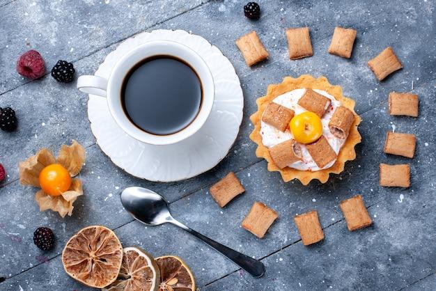 Bovenaanzicht van kopje koffie met romige cake kussen gevormde koekjes samen met bessen op grijs bureau