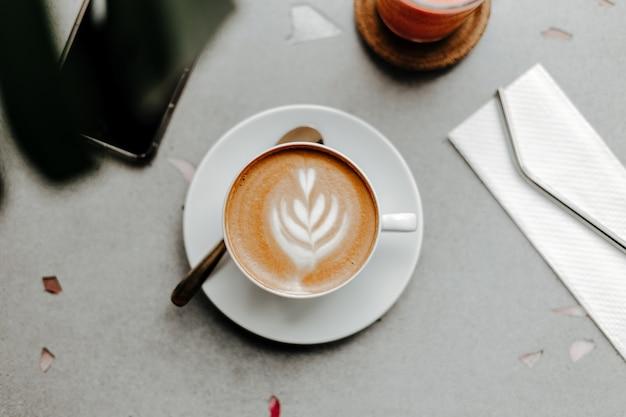 Bovenaanzicht van kopje koffie met schuim en room, plastic rietje op servet en telefoon op marmeren lichttafel