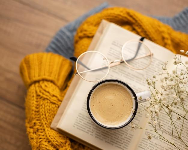 Bovenaanzicht van kopje koffie op boek met bril en trui