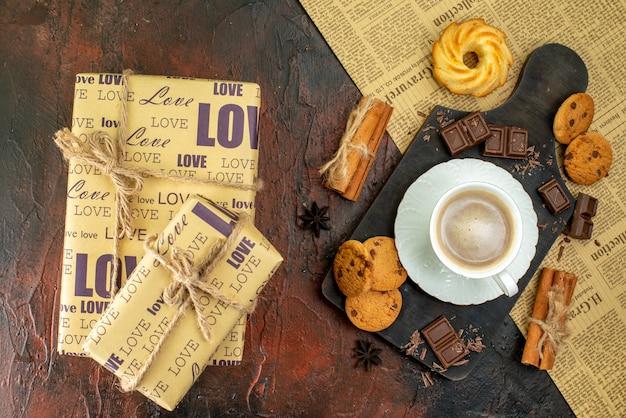 Bovenaanzicht van kopje koffie op houten snijplank op een oude krant cookies kaneel limoenen chocoladerepen mooie geschenkdozen op donkere achtergrond