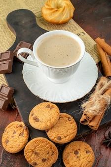 Bovenaanzicht van kopje koffie op houten snijplank op een oude krant cookies kaneel limoenen chocoladerepen op donkere achtergrond