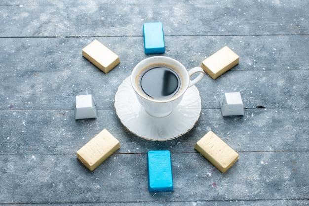 Bovenaanzicht van kopje koffie warm en sterk met beklede goud gevormde chocolade op lichtblauw bureau, koffie cacao drankje warm