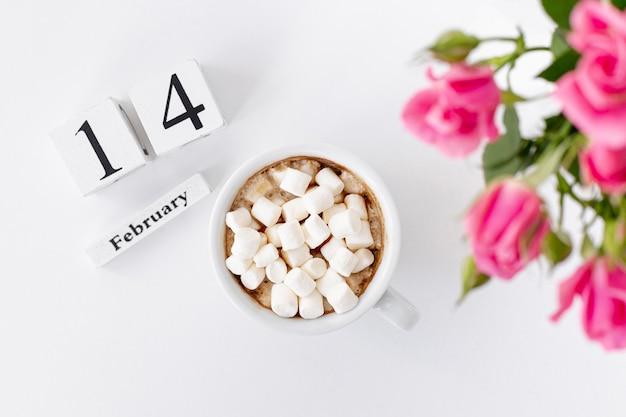 Bovenaanzicht van kopje marshmallows met rozen en datum