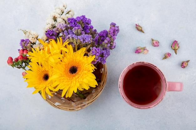 Bovenaanzicht van kopje thee en bloemen in mand en op wit