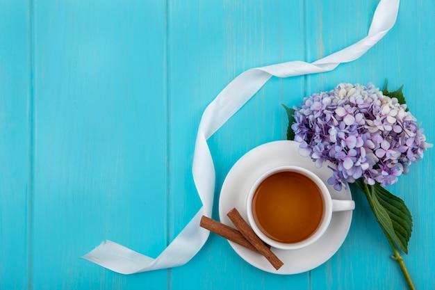 Bovenaanzicht van kopje thee en kaneel op schotel met bloem en lint op blauwe achtergrond met kopie ruimte
