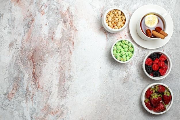 Bovenaanzicht van kopje thee met aardbeien en noten op witte ondergrond