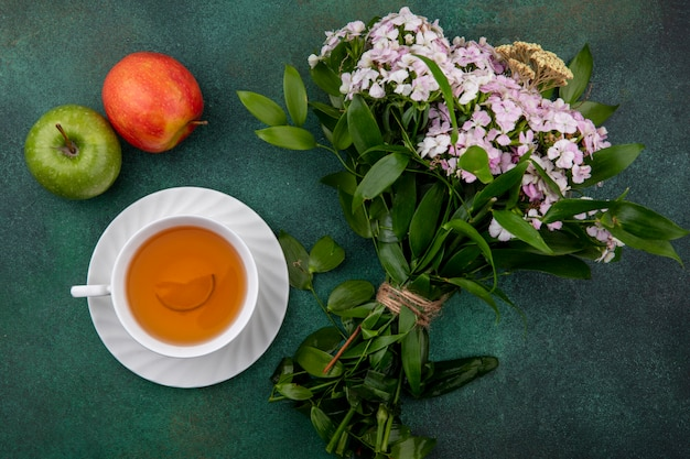 Bovenaanzicht van kopje thee met appels en een boeket bloemen op een groene ondergrond