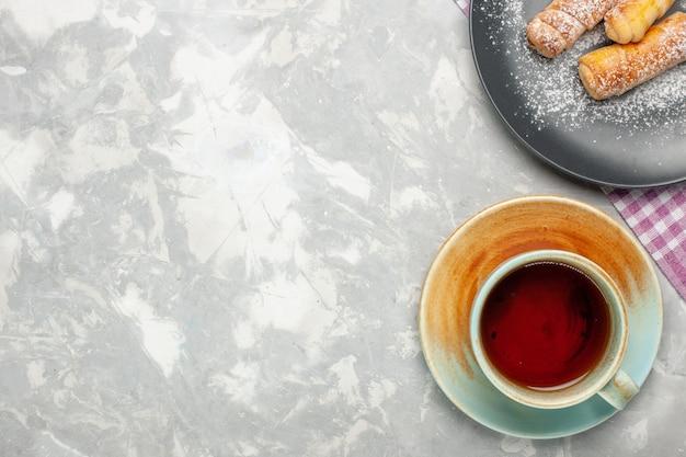 Bovenaanzicht van kopje thee met bagels op witte ondergrond