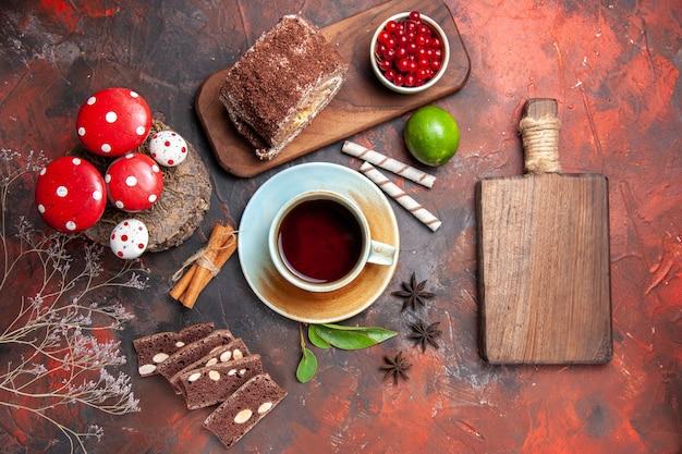 Bovenaanzicht van kopje thee met cake en koekje roll op donkere ondergrond