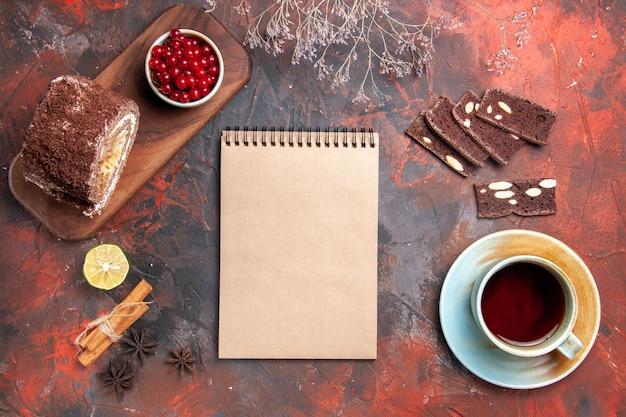 Bovenaanzicht van kopje thee met cake en koekje rollen op donkere ondergrond