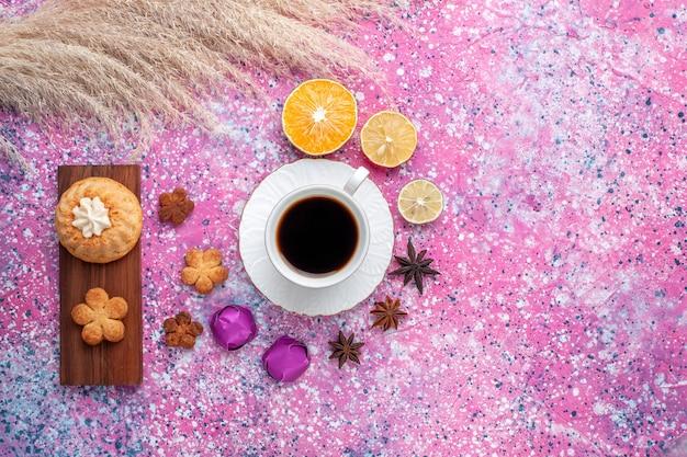 Bovenaanzicht van kopje thee met cake en koekjes stukjes sinaasappel op roze oppervlak