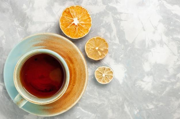 Bovenaanzicht van kopje thee met citroen op witte ondergrond