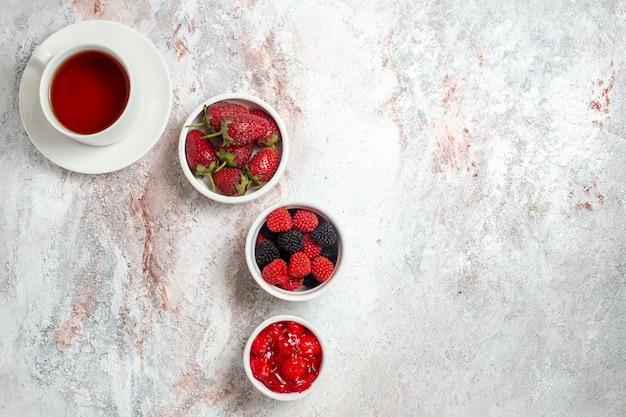 Bovenaanzicht van kopje thee met confitures en jam op witte ondergrond