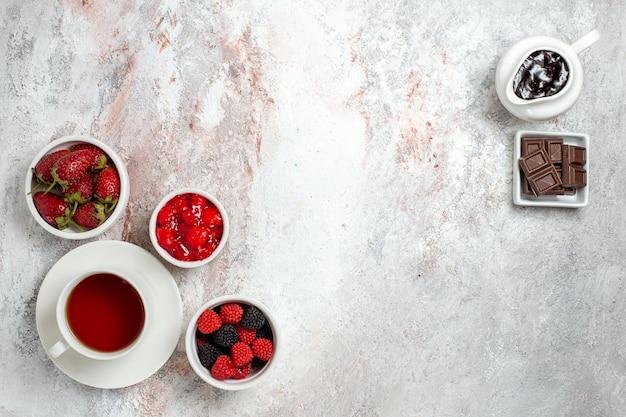 Bovenaanzicht van kopje thee met confitures jam en chocolade op een wit oppervlak